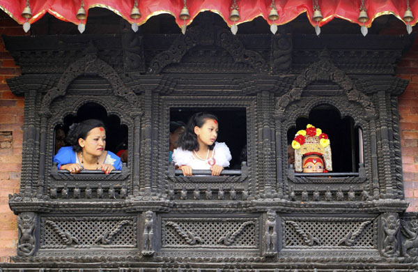"ATTENTION EDITORS -- THIS IMAGE IS 20 OF 29 TO ACCOMPANY NEPAL-GOD/CULTURE, A PICTURE PACKAGE ON NEPALI BOY SAMBEG SHAKYA. SEARCH KEYWORD ""GANESH"" TO SEE ALL IMAGES PXP01-29 Sambeg Shakya, 6, observes the Indra Jatra Festival from a window of a house of the Living Goddess Kumari in Kathmandu September 16, 2011. Sambeg Shakya was hailed last year by Buddhist priests as Ganesh, or the god of good fortune, since when he has led several processions of Nepal's better-known 'living goddesses', also known as Kumari. The centuries-old ritual, once used by now-toppled kings who thought it would make them stronger, was the climax of the annual Hindu festival of Dasain, which lasts for two weeks and has become a major tourist attraction in Nepal.  Sambeg will continue in his supporting role until he is big enough to fit in a chariot pulled by men, after which he must return to real life. Picture taken September 16, 2011. REUTERS/Navesh Chitrakar (NEPAL - Tags: RELIGION SOCIETY POLITICS)"