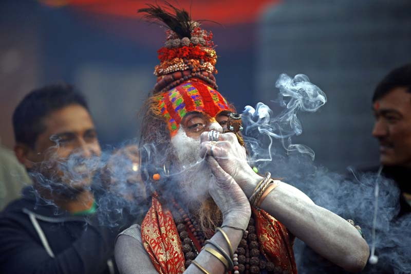 Sadhu smokes in Pashupatinath Temple for Mahashivaratri